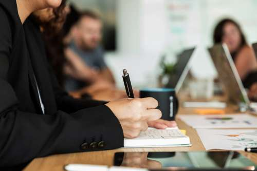 Woman Writing In Notebook During Meeting Photo