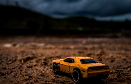 Yellow Toy Car In Dramatic Desert Landscape Photo