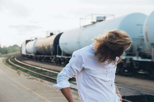 Young Man By Trains At Sunset Photo