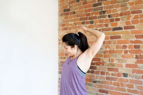 Young Woman Exercising In Workout Clothes Against Brick Wall Photo