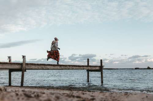Young Woman In Autumn Clothing Running Across Dock Photo