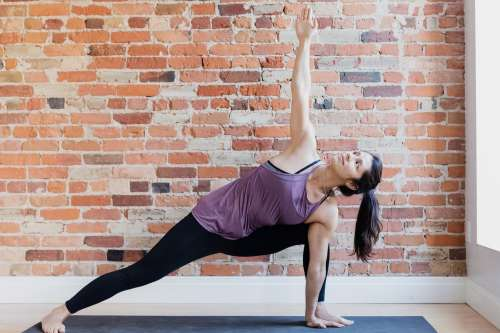 Young Woman In Yoga Position Against Exposed Brick Photo