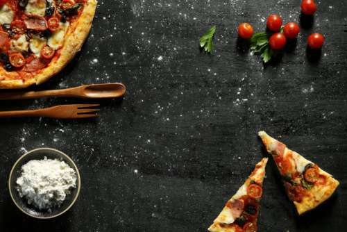 Messy pizza on a black table