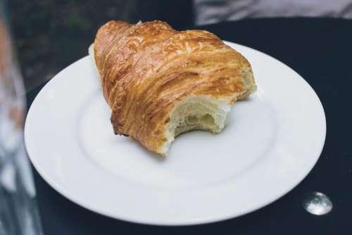 Bitten butter croissant on a plate
