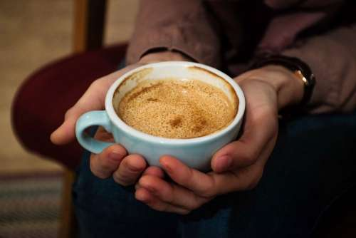 Cup of flat white in female hands