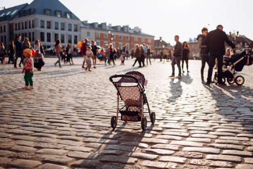 An empty stroller in a crowded Old Town square