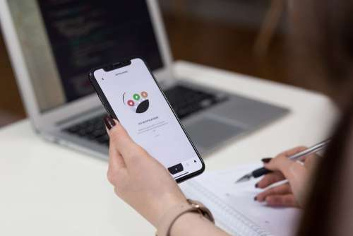 A female holding an iPhone X and taking notes 3