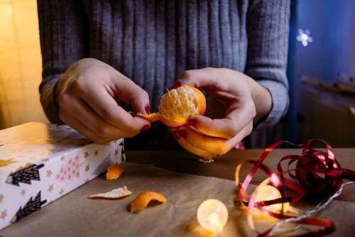 A female peeling a mandarin in a festive setting