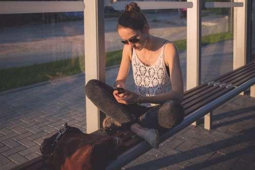 Girl sitting at tram stop