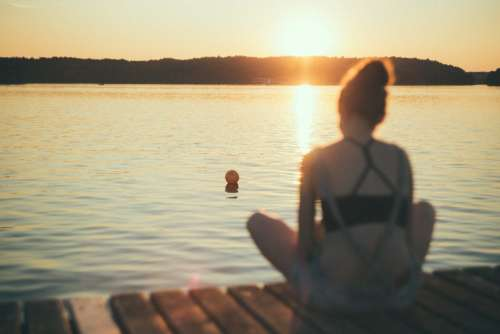 A girl sitting on a pier blurred