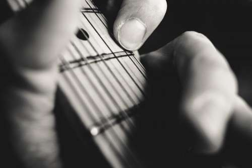 Guitarist hand playing guitar closeup