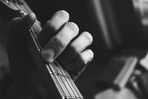 Guitarist hand playing guitar in black and white