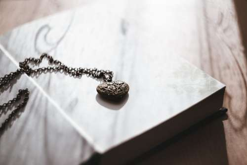 Heart necklace on an open book