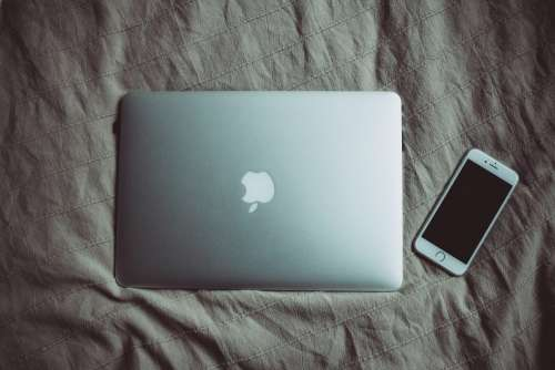 MacBook and iPhone on bed