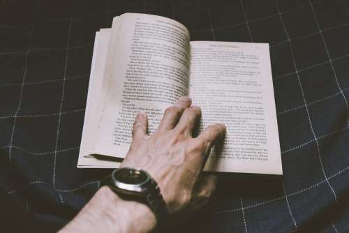Male hand holding an open book