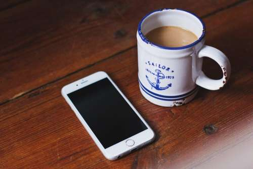 Oldschool mug of latte and an iPhone