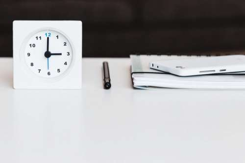 A table clock, a planner and a phone