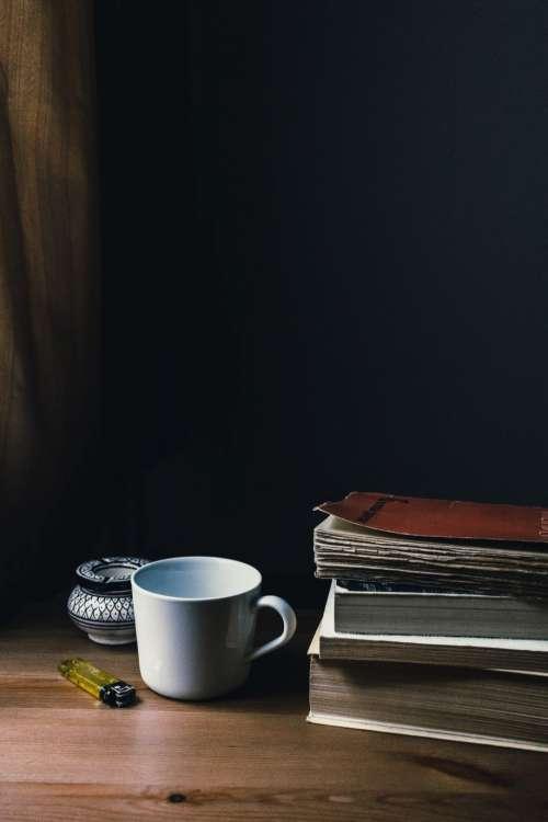 Tea mug, a lighter and a pile of books