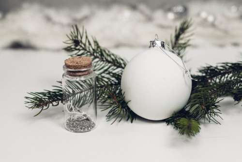 White and silver bauble with a spruce twig