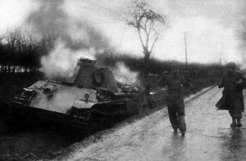 American Soldier escorting German  Crewman from burning Panther Tank during the Battle of the Bulge free photo