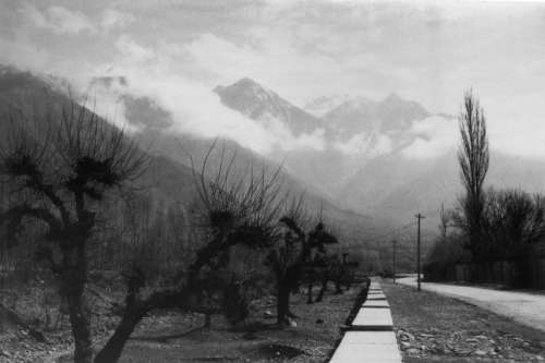 Black and White photo with path into the mountains with clouds in Srinagar, India free photo