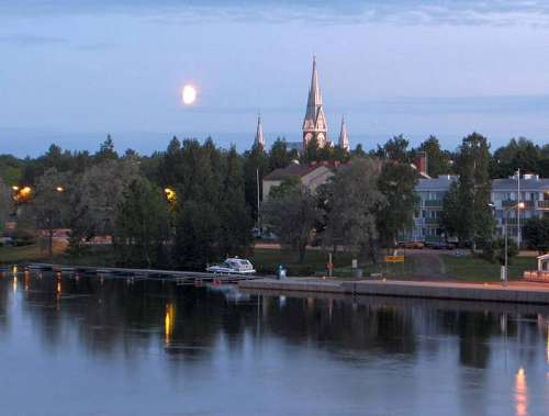 Church of Joensuu on the riverbank under the midnight sun in Finland free photo