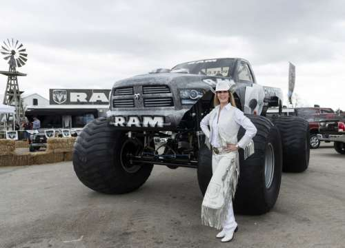 Cowgirl dressed in white standing next to monster truck in Texas free photo