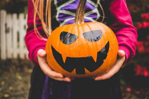 Girl holding Jack-O-Lantern Halloween Pumpkin scary face free photo