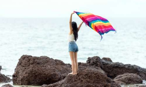 Girl standing on a rock with blanket on the seashore in the Maldives free photo