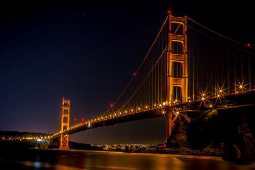 Golden Gate Bridge over the bay at night illuminated in Gold in San Francisco, California free photo