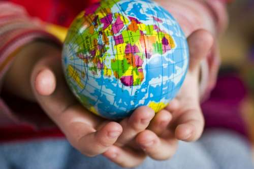 Hands holding small globe of earth free photo