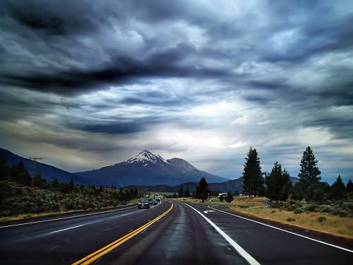 Highway Road into the mountains under heavy clouds free photo