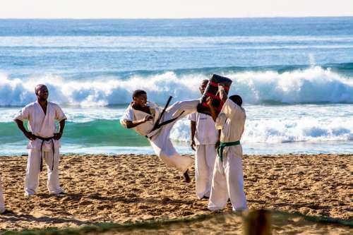 Karate Fighter Jump Kicking on Beach free photo