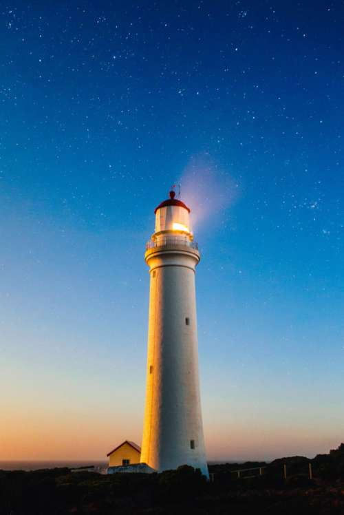 Lighthouse beneath the sky and stars with light on free photo
