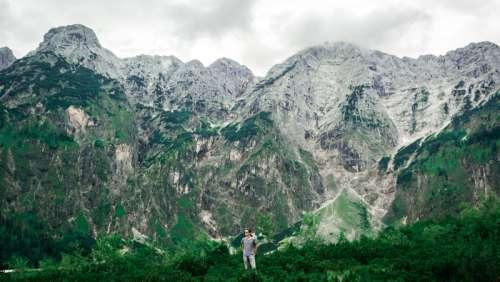 Man Standing Beneath Tall Mountains in Austria free photo