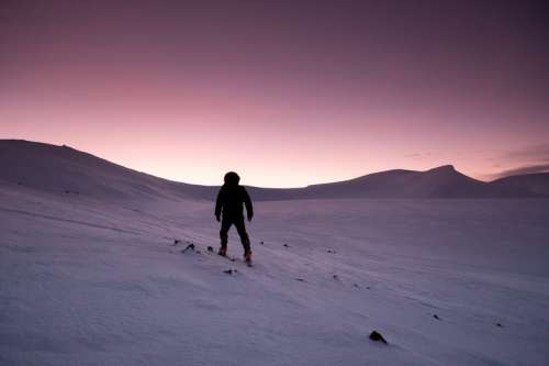 Purple Sunset in the winter of person hiking in the snow in Quebec, Canada free photo