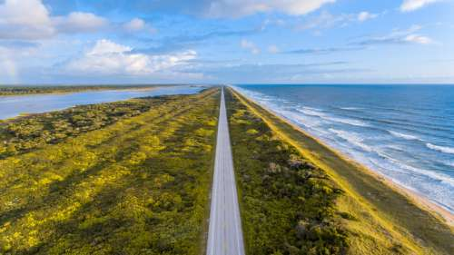 Road between the sea and lake free photo