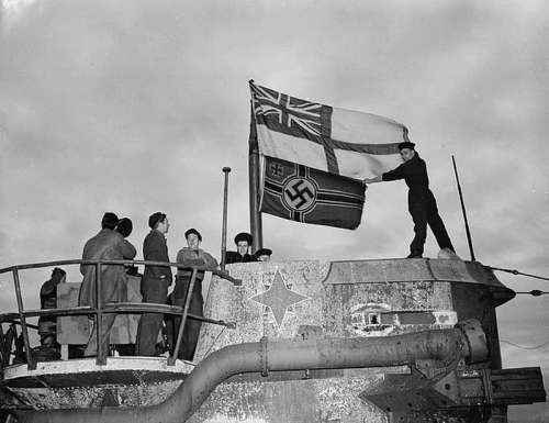 Seamen raise the White Ensign over a captured German U-boat in World War II free photo