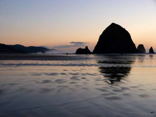 Silhouette of Large Rocks rising out of the Ocean at dusk in Oregon free photo