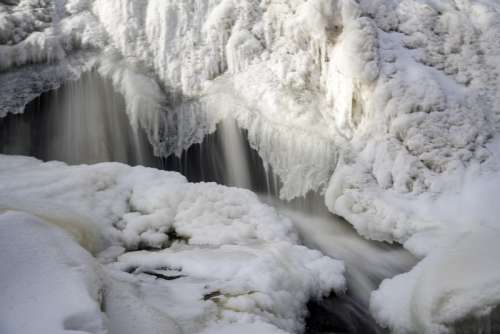 Smooth Water Cascading over frozen Waterfalls at Gooseberry Falls State Park, Minnesota free photo