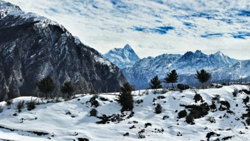 Snow-capped mountains with clouds overhead in Auli, India free photo