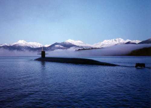 Submarine surfacing with mountains in the landscape free photo