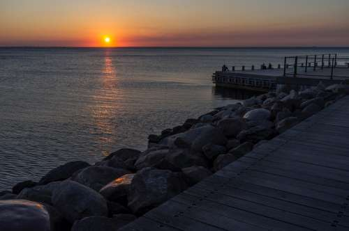 Sunset over the ocean at the shore and docks in Malmo, Sweden free photo