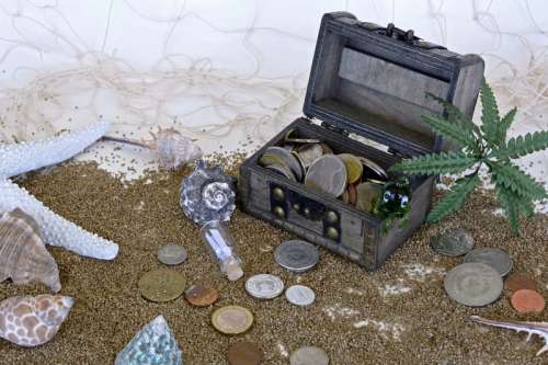 Treasure Chest with Coins in the Sand free photo