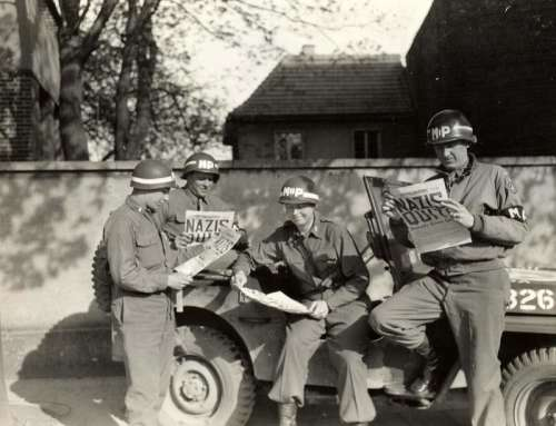 US military policemen read about the German surrender ending World War II in Europe free photo