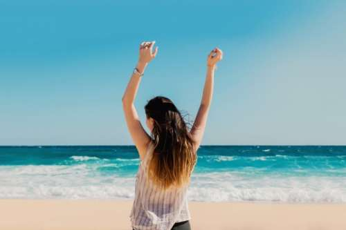 Girl is standing on the beach with hands up