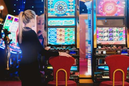 Woman is ready to play at slot machine in casino