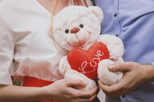 Young couple holding toy teddy bear and celebrating Valentine's Day