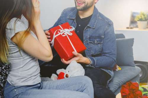 The guy gives a gift box to his girlfriend