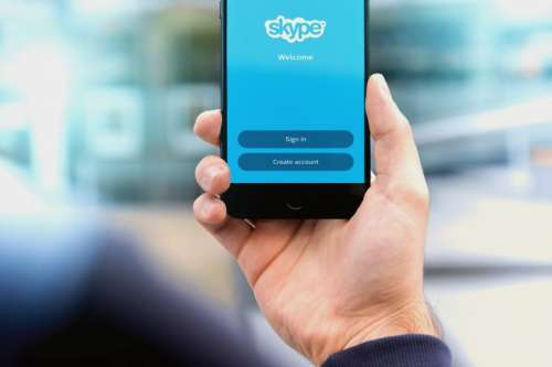 Man holding smartphone with Skype app